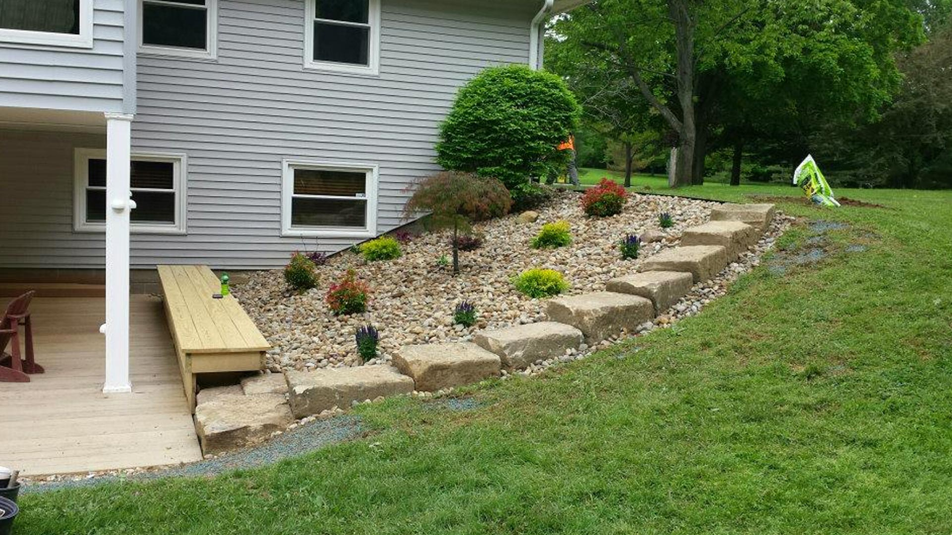 Landscaping with large boulders and river rock installed in Geneva, OH.